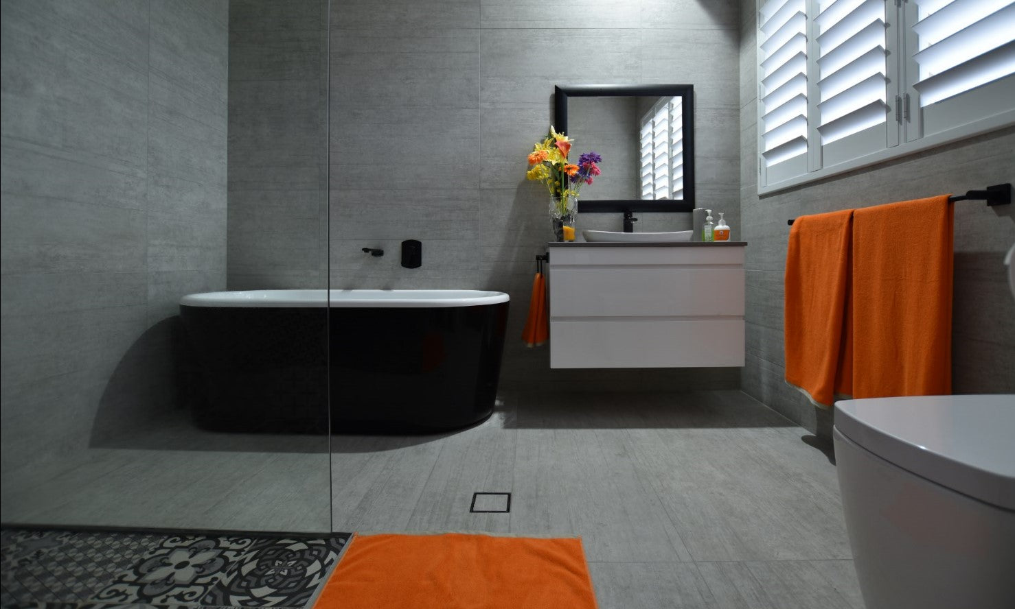 Bathroom uses large format tiles, wall hung vanity and a walk in shower for low maintenance cleaning design