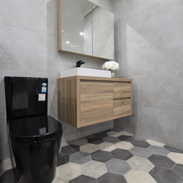Bathroom tile display at ATS Showroom featuring light grey concrete look porcelain, black toilet and hex tiles