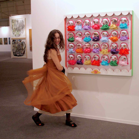 Alex Mitchell in a playful pose in front of her artwork Beauty Queen on display in a group show at an international art fair.