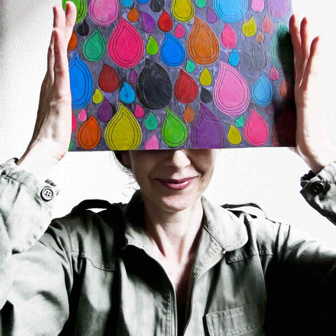 Alex Mitchell posing with her original colorful artwork used to create the playful Dripdrop print used on Twinki-Winki products.