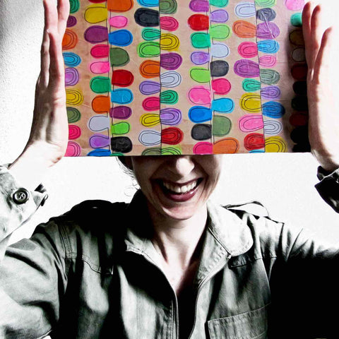 Alex Mitchell posing with her original colorful artwork used to create the playful Flipflop print used on Twinki-Winki products.
