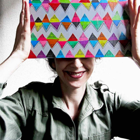 Alex Mitchell posing with her original colorful artwork used to create the playful Zigzag print used on Twinki-Winki products.