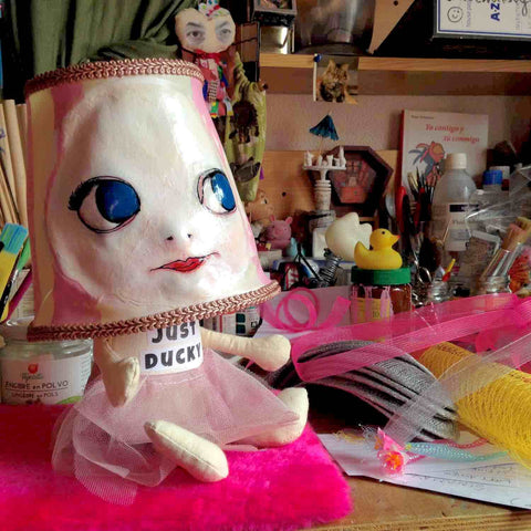 Funny doll with a lampshade head sitting on a busy studio table surrounded by colorful materials, objects, papers, and tools.