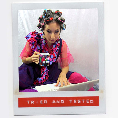 Alex Mitchell all dressed up drinking coffee while checking her emails with curlers in her hair feeling fab with boa scarf.