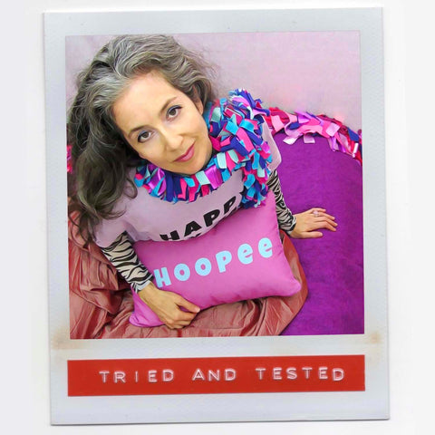 Alex Mitchell all dressed up in colorful setting feeling fab with her boa scarf and with Whoopee slogan pillow on her lap.
