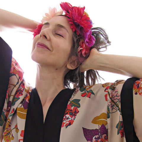 Alex Mitchell wearing floral kimono and flower crown feeling fab tilting head back smiling with eyes closed.