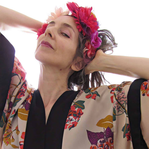 Alex Mitchell wearing floral kimono and flower crown feeling fab tilting head back with a knowing look at camera.