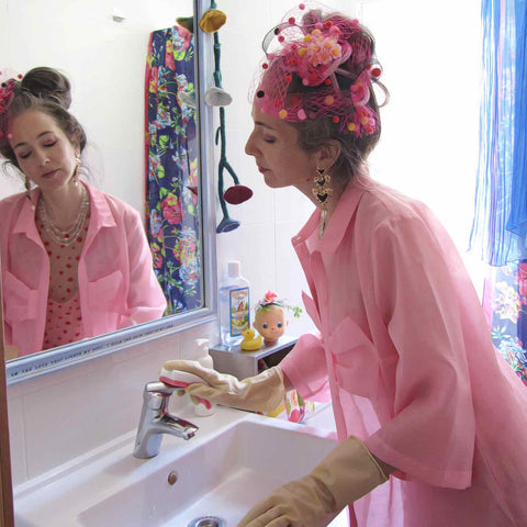 Alex Mitchell cleaning bathroom sink, all dressed up in pink with her misfit attitude about feeling fab whenever she wants.