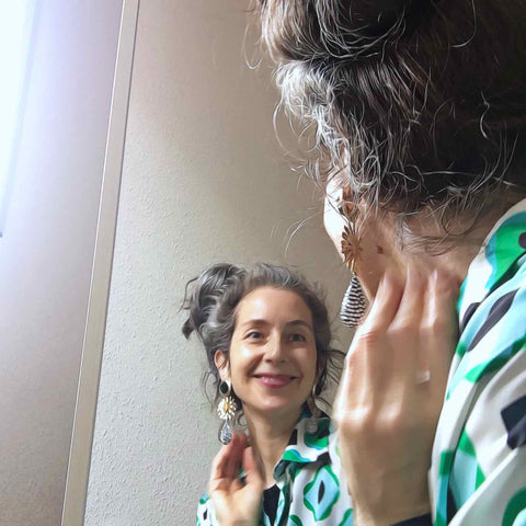 Alex Mitchell wearing colorful blouse and looking in the mirror while putting on earrings feeling happy with her outfit.