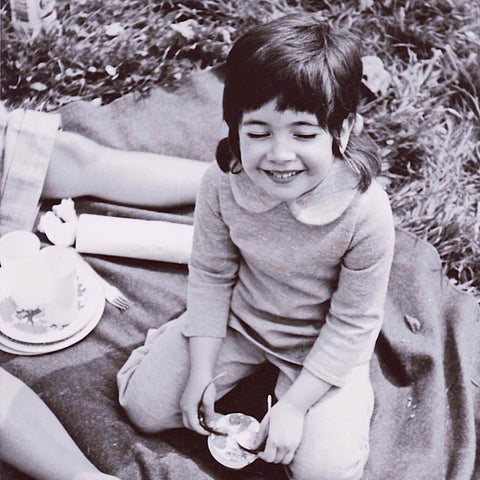 Alex Mitchell of the Twinki-Winki online fashion brand as a little kid, sitting and smiling to herself with eyes closed.