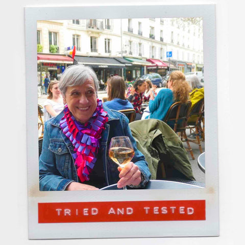 Pat feeling fab wearing her happy multicolor fashion boa scarf with style while having a glass of wine in a Paris cafe.