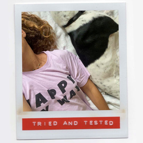Paty relaxing while wearing her comfy soft cotton tee lying down next to her dog happy at home.
