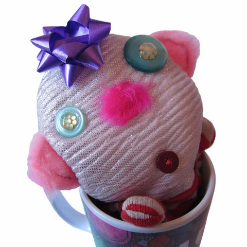 A cute fabric doll with a pink nose, button eyes, and gift ribbon on its head is poking out of a Twinki-Winki coffee mug.