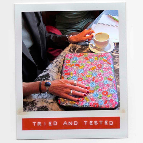 Colorful graphic laptop sleeve on marble table with stylish hands of owner who is working from a cafe.