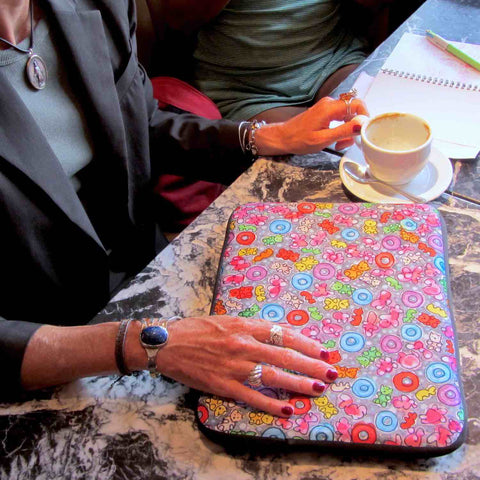 Colorful graphic laptop sleeve on marble table with Laila's stylish hands on top while she's preparing to work from a cafe.