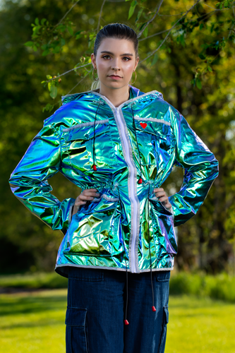 Image of a woman wearing a metallic green women's mid-season jacket with the hood down.