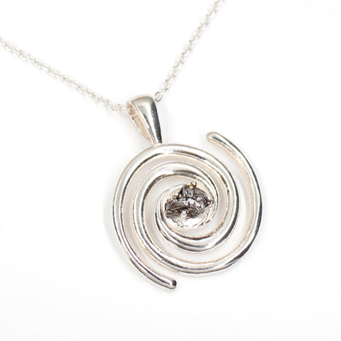 Spiral galaxy necklace with a genuine Campo del Celio meteorite in the center! A solid sterling silver spiral galaxy necklace is the perfect space gift. Shown on white background.
