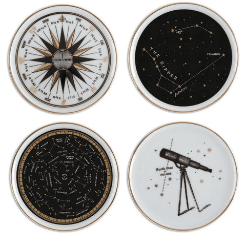 A set of four porcelain, white, black and gold astronomy/space-themed drink coasters showing stars, constellations, a telescope, and a compass rose.