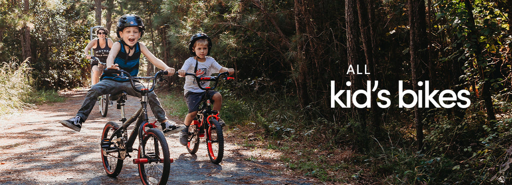 "All Kid's Bikes | Two boys are riding bikes with their mother. The older boy rides a 18"" Boy's Kent Abyss without training wheels and his brother rides a Razor DSX"