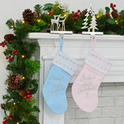 blue and pink baby's first christmas stockings hanging from stocking hangers