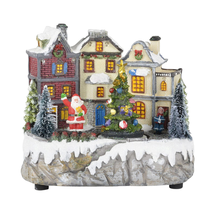 christmas village scene with mini snow flocked christmas trees and houses decorated with wreaths and garlands