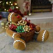 gingerbread man basket decoration on coffee table filled with christmas gift bows and ribbons