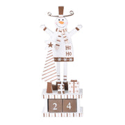 wooden block snowman calendar featuring brown countdown blocks, with snowman standing behind christmas tree and gifts