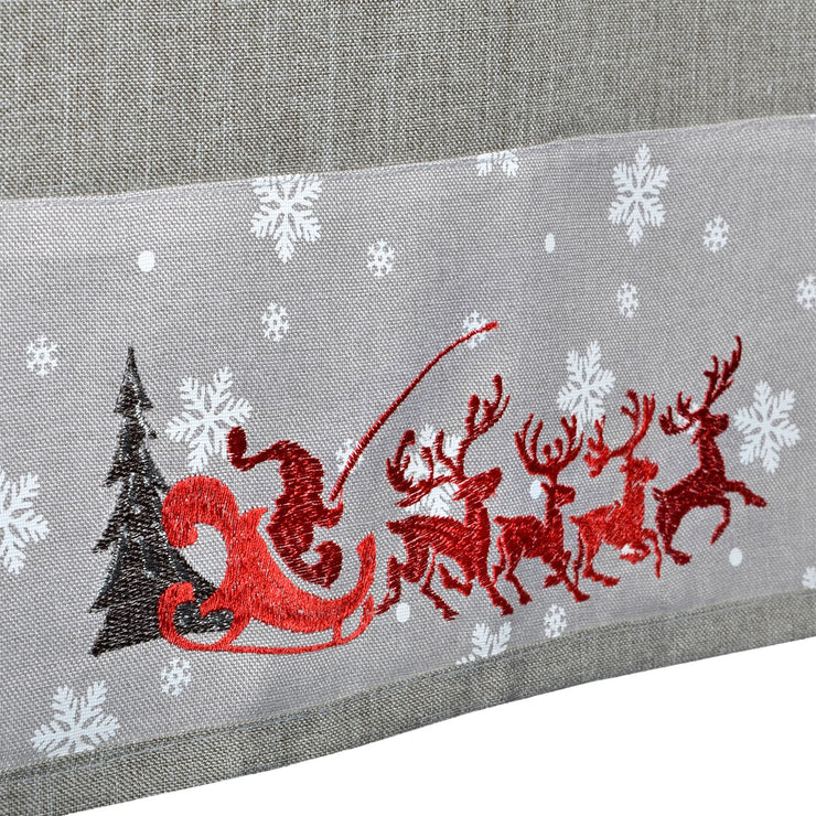 close up of red embroidered santa in sleigh with reindeer detail, and grey christmas tree with printed white snowflakes