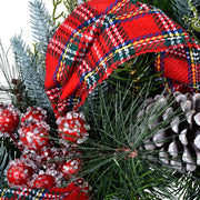 close up of tartan bow with snow covered berry clusters and silver finished pine cones