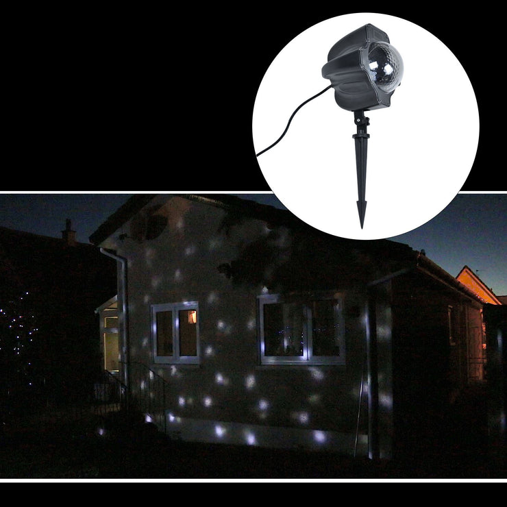 LED snowfall projector, projected onto house at night time