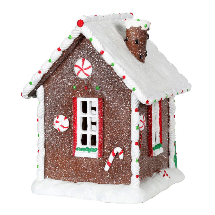 side view of gingerbead house with candy cane and frosted icing edging
