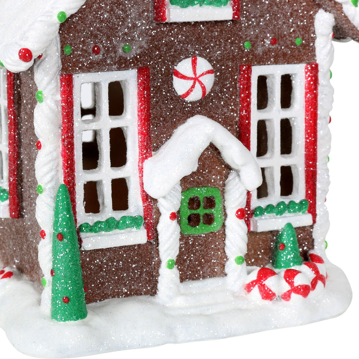 close up detail of gingerbread house door and window with mini glitter christmas tree