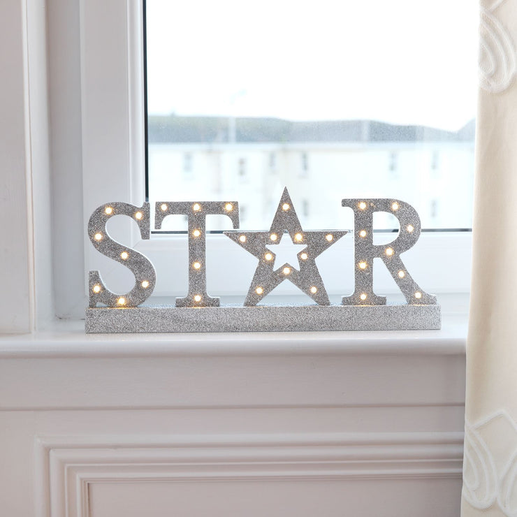 silver star christmas wooden sign on window ledge in lounge