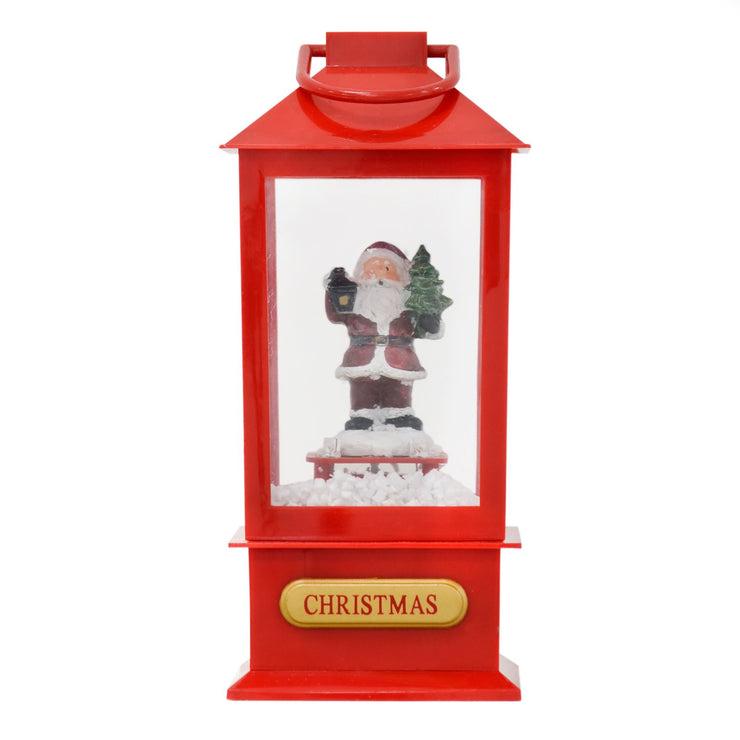 front view of red musical lantern with santa holding mini tree and lantern and &