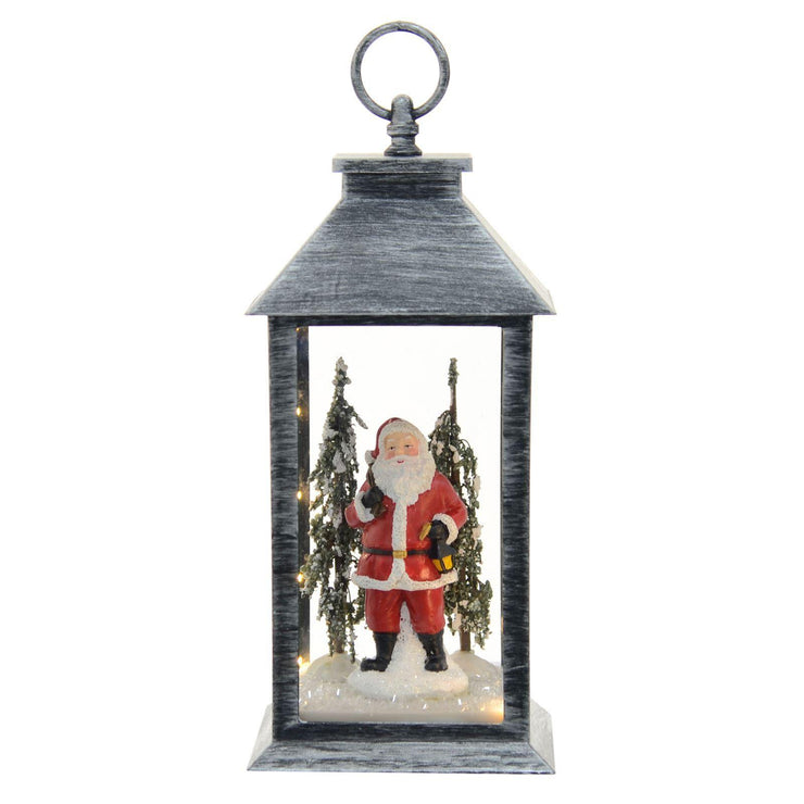 silver christmas lantern decoration with mini led lights, santa holding lantern character and snowflocked trees