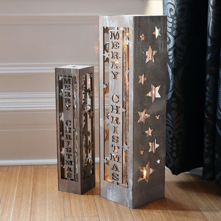 merry christmas led pillar decoration set on living room floor in front of curtains and wall panelling