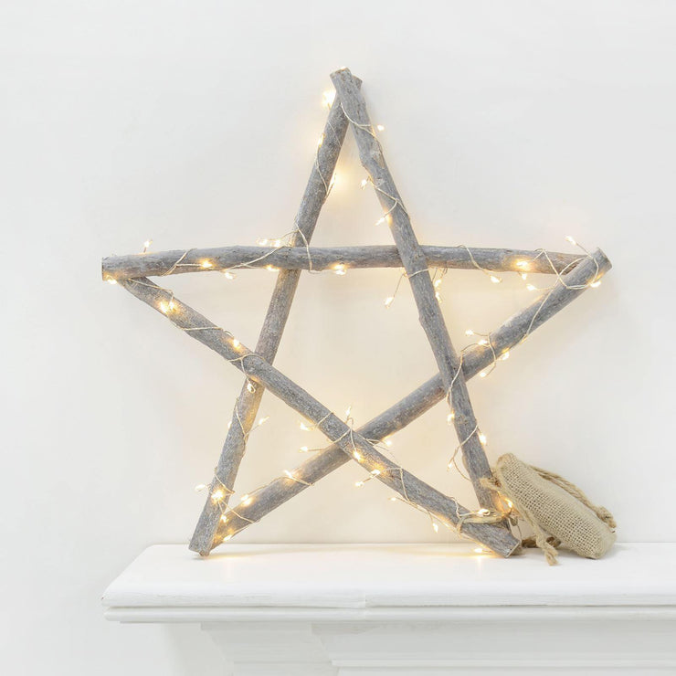 wooden star with led string lights and hessian battery bag on fireplace