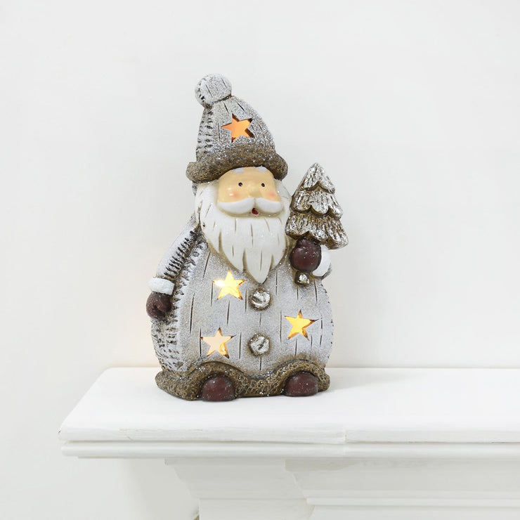 "9"" light up santa decoration with mini snow covered tree and warm white lights on fire ledge"