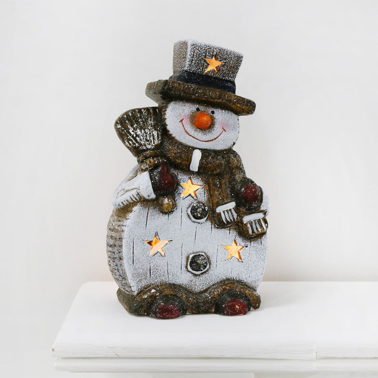 front view of snowman ceramic figure with broomstick and warm white led lights
