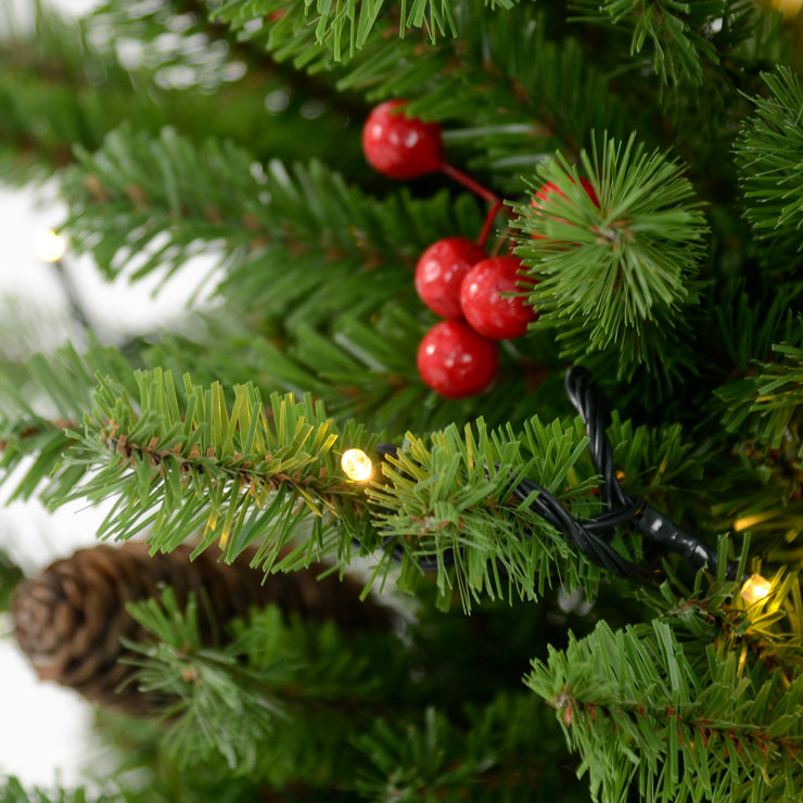 close up of berries, pine cones and warm white led lights
