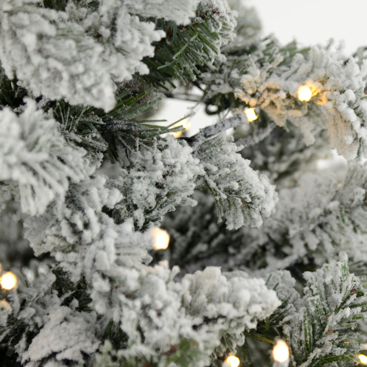 close up detail of snow flocked branches and warm white lights
