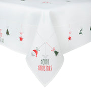 close up detail of embroidered christmas tablecloth featuring santa head, christmas bell, christmas tree and star design