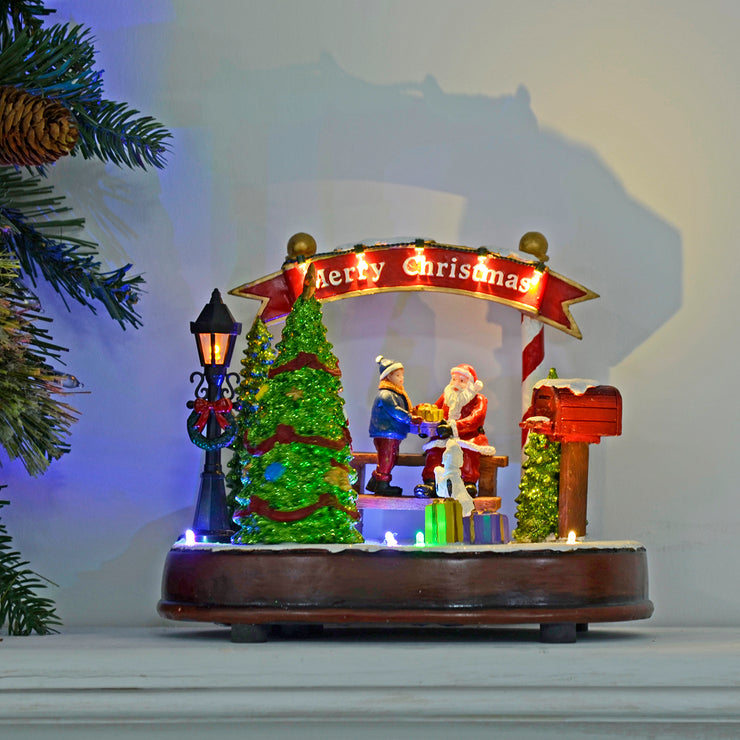 light up christmas scene on fire place mantel with christmas tree to the side