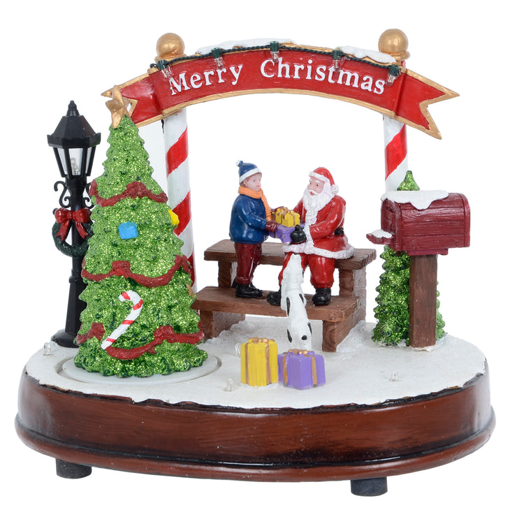 front view of christmas scene featuring rotating glitter christmas tree with santa giving a gift to a child and small dog looking on