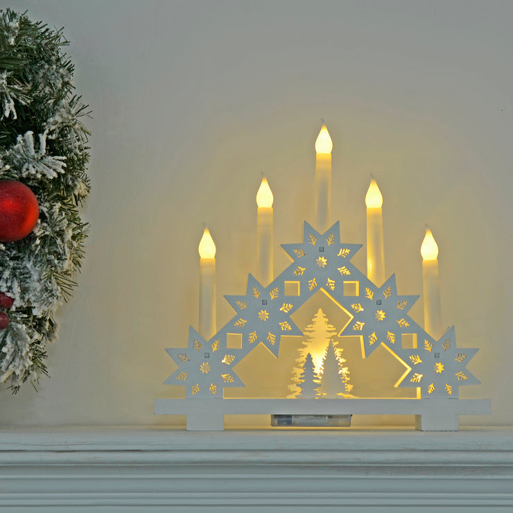 warm white candle arch on fireplace mantel in living room