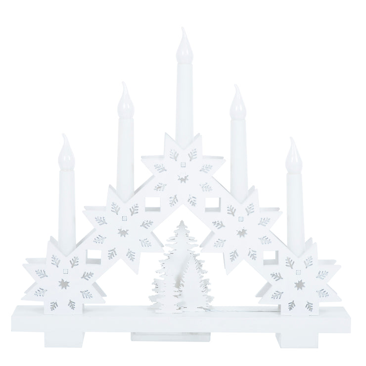 front view of white wooden candle arch bridge featuring 5 led candles and wooden snowflake and tree design