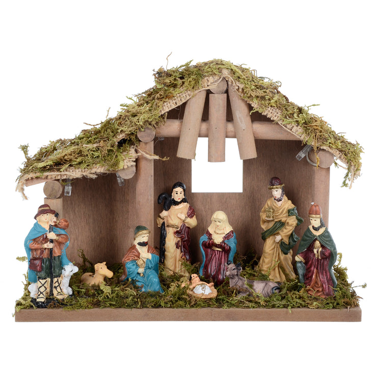 front view of nativity scene decoration with moss covered barn and christmas characters from baby jesus birth