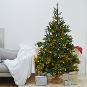 christmas tree in living room area beside sofa with gifts placed under tree