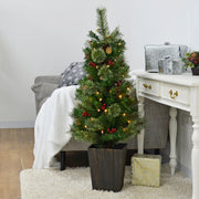 pre lit potted christmas tree with pine cones and berries in lounge setting