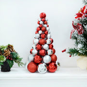 red and silver christmas tree shaped decoration crafted from glitter, matte and shiny baubles on console table